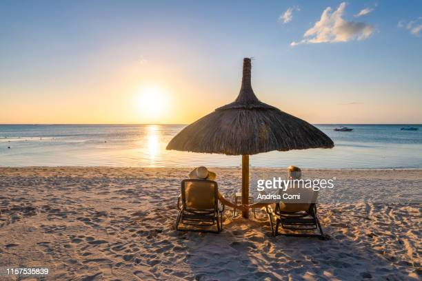 a young couple holding hands admires the sunset in a tropical beach - vacances à la mer photos et images de collection