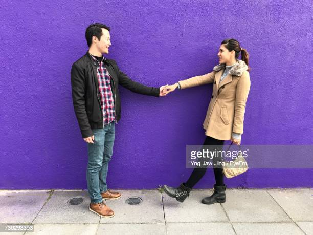 Young Couple Holding Hands Against Purple Wall