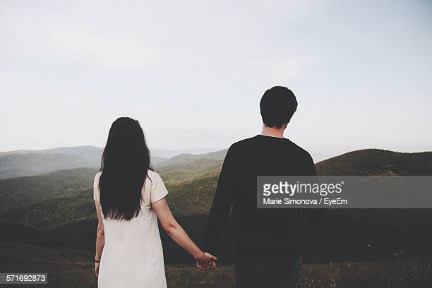 Young Couple Holding Hands And Looking At Scenic View In Mountains