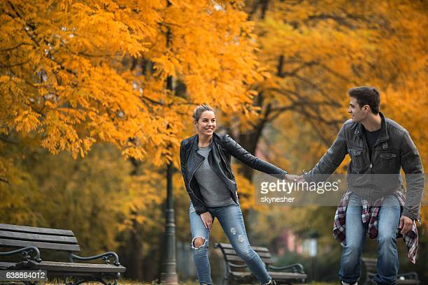 Young couple holding hands and roller skating through autumn park.