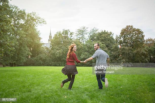 Young couple holding hands and running outdoors