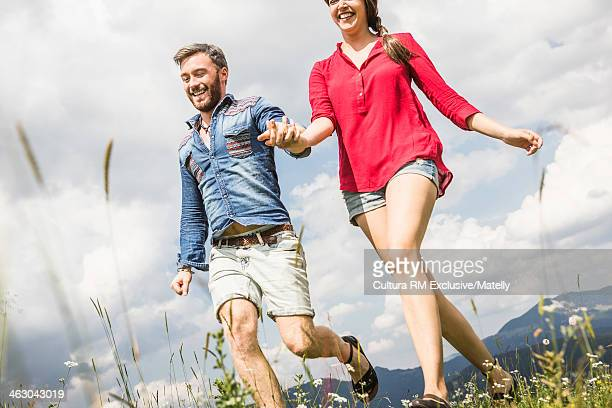 Young couple holding hands and running, Tyrol, Austria
