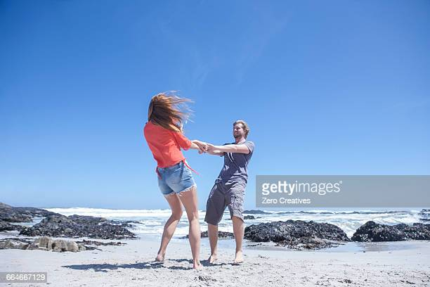 Young couple holding hands and spinning each other around on beach, Cape Town, South Africa