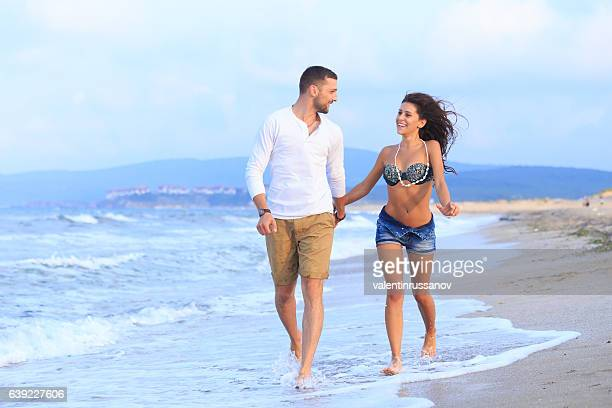young couple holding hands and walking on beach - honeymoon stock pictures, royalty-free photos & images
