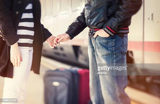 Pareja joven sosteniendo las manos en la estación de tren