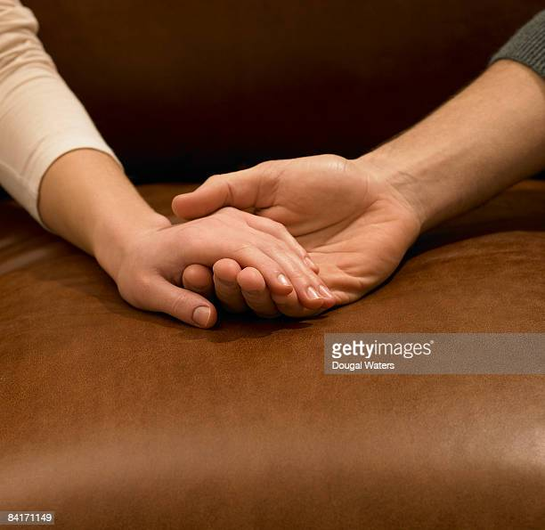 Young couple holding hands, close up.