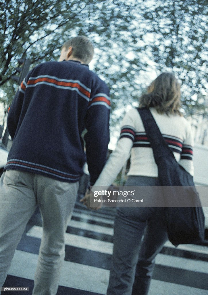 Young couple holding hands crossing on pedestrian crossing, rear view : Stock Photo