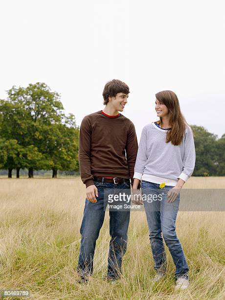 Young couple holding hands in a field