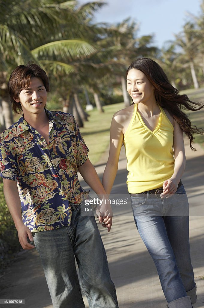 Young Couple Holding Hands in a Park : Stock Photo