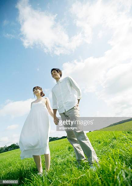 Young couple holding hands in field