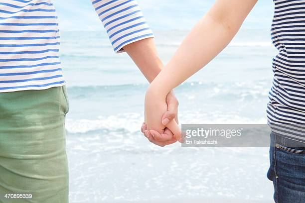 Young couple holding hands in front of sea