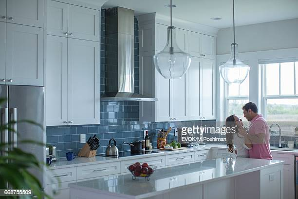 Young couple holding hands in kitchen