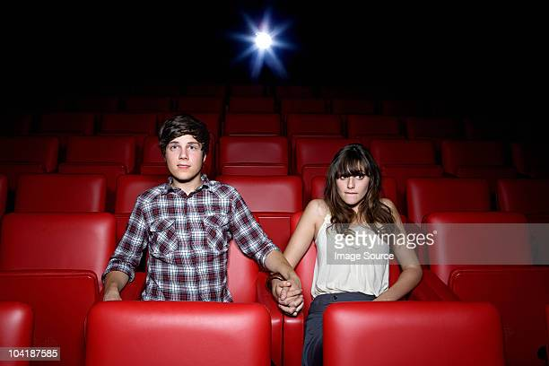 Young couple holding hands in movie theater