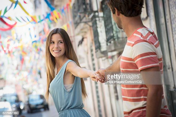 Young couple holding hands in old town, Lisbon, Portugal