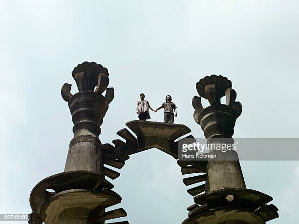 young couple holding hands on a surreal structure - las posas stock pictures, royalty-free photos & images