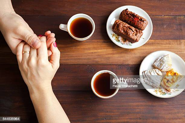 Young couple holding hands over coffee table