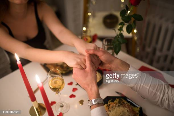 young couple holding hands - valentines day dinner stock pictures, royalty-free photos & images