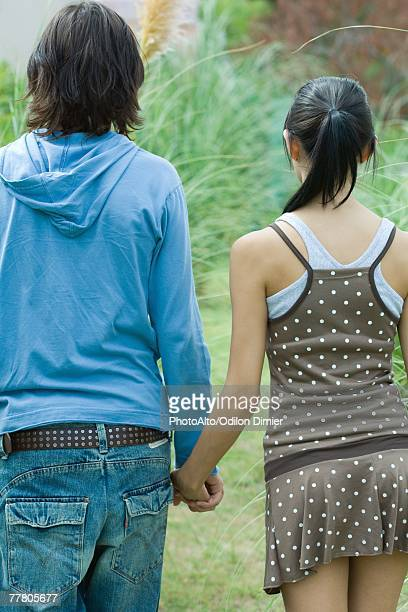 young couple holding hands, rear view - teen mini skirt stock photos and pictures