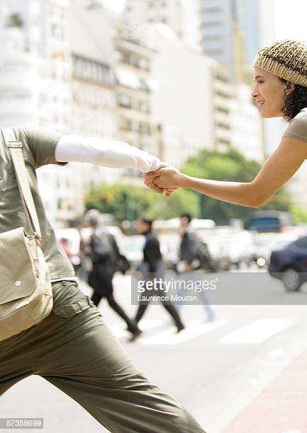Young couple holding hands, running across street