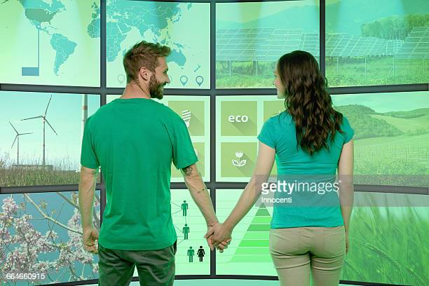Young couple holding hands, standing in front of graphical screens, displaying environmental images