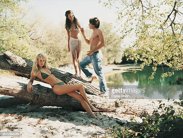 Young Couple Holding Hands Standing on a Log and a Serious Excluded Woman Lying Looking at the Camera