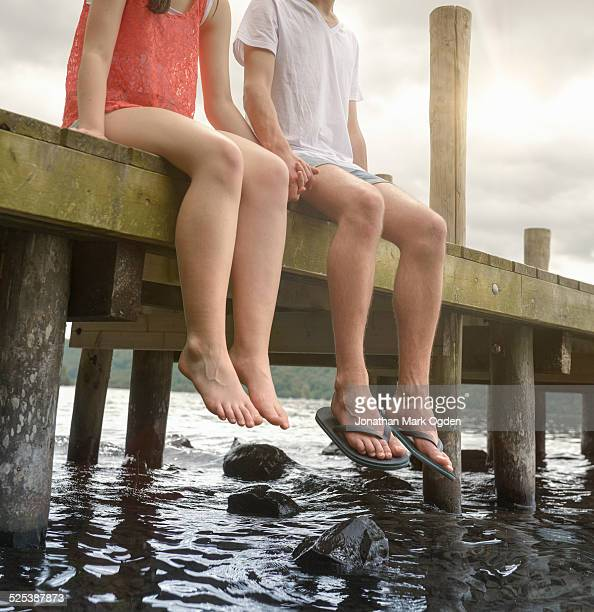 young couple holding hands together and sitting on edge of jetty over lake - ragazzine scalze foto e immagini stock