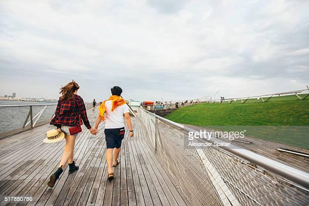 Young couple holding hands walking on Osanbashi Pier in Yokohama, Japan