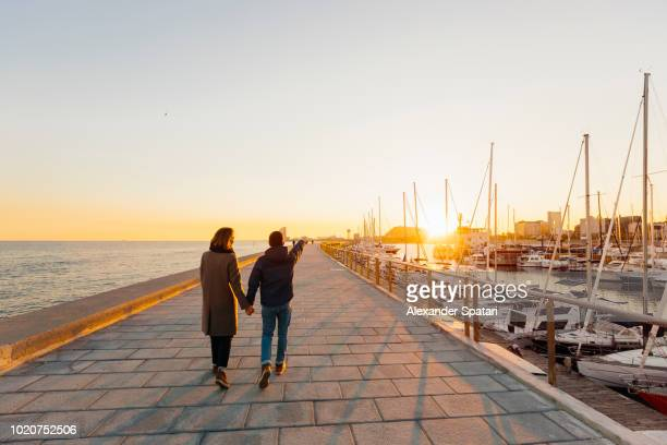 Young couple holding hands walking towards sunset in Barcelona, Spain