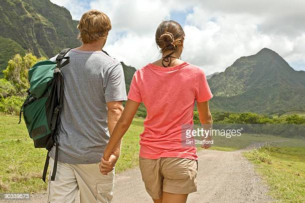 young couple holding hands while hiking in valley - valley stock pictures, royalty-free photos & images