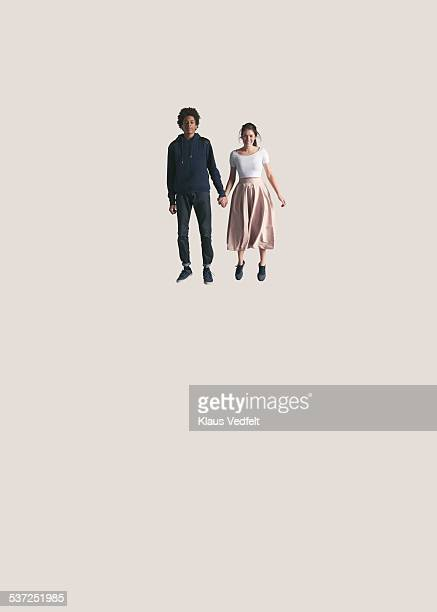 Young couple holding hands while jumping
