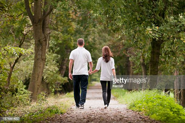 Young couple holding hands while walking on park path