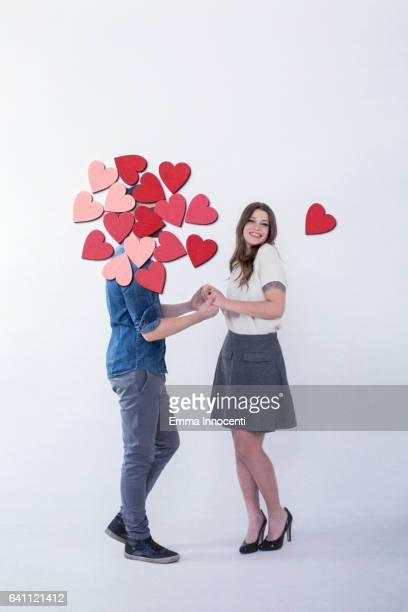 Young couple holding hands with hearts around his head