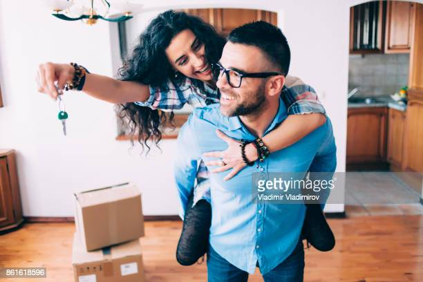 young couple holding keys of new apartment - coppia di giovani foto e immagini stock