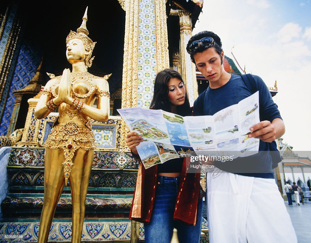 Young Couple Holding Map by Palace : Stock Photo