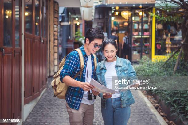 young couple holding map while standing on city street - asia map stock pictures, royalty-free photos & images