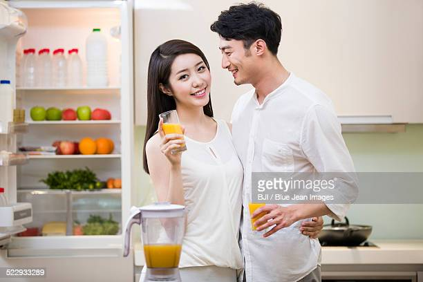 Young couple holding orange juice in kitchen