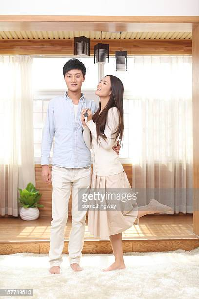 Young Couple Holding Out New House Keys