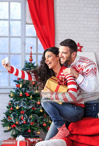 Young couple holding present and making selfie at home
