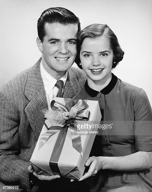 Young couple holding present, posing, (B&W)