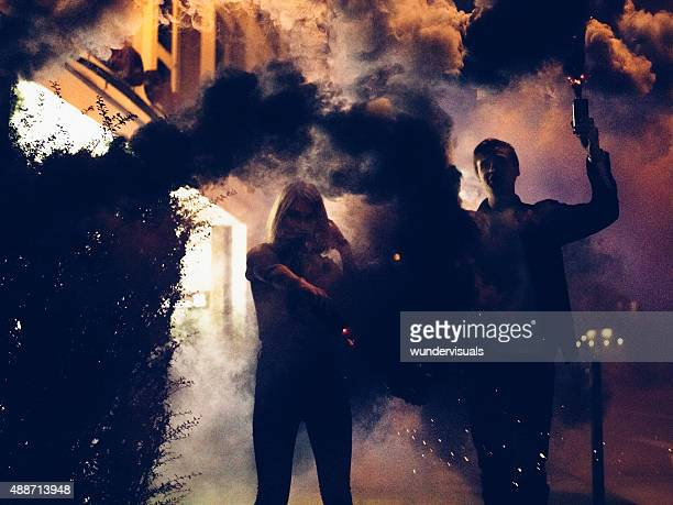Young couple holding smoke flares at night in the city