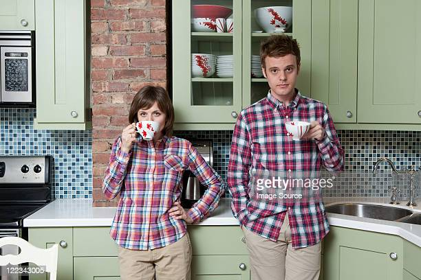 young couple holding teacups in kitchen - mimica fotografías e imágenes de stock