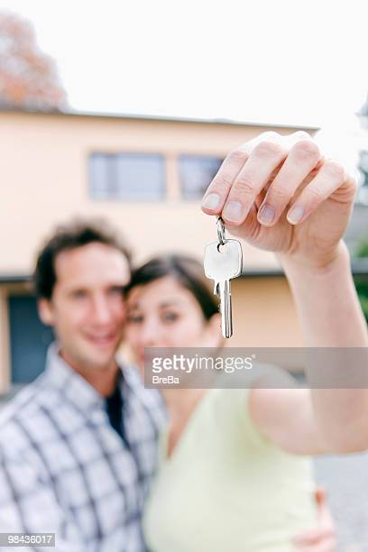 young couple holding the keys to their new home