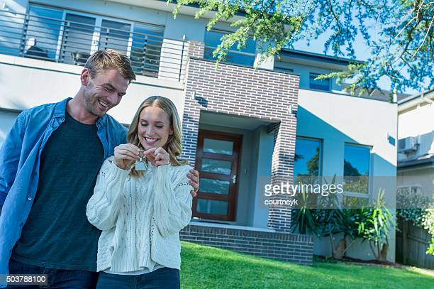 Young couple holding their new house key.