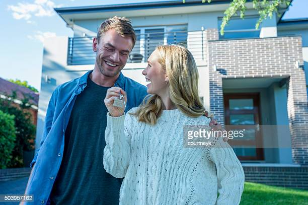 young couple holding their new house key. - home ownership stock pictures, royalty-free photos & images