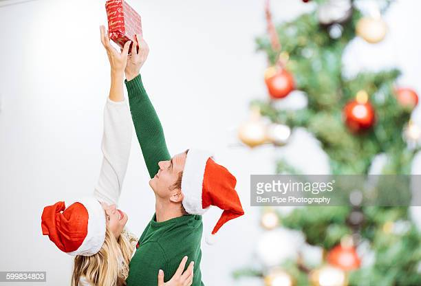 Young couple holding up and reaching for christmas present