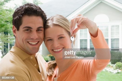 Young Couple Holding Up Key To New House Stock Photo