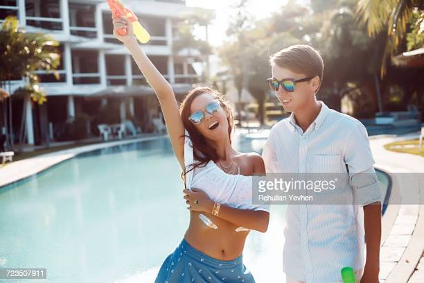 Young couple holding up water gun on poolside, Koh Samui, Thailand