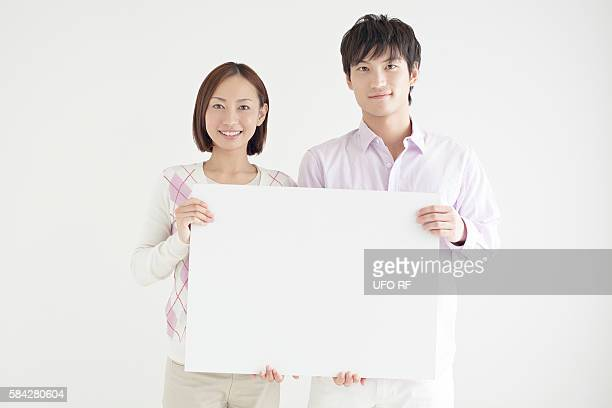 Young couple holding whiteboard