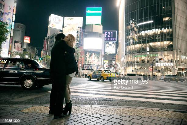CONTENT] A young couple hug at Shibuya's busy Scramble Intersection