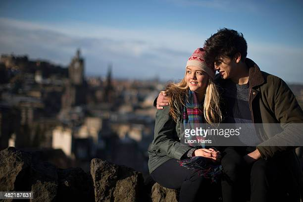 a young couple hug on calton hill with the background of the city of edinburgh, capital of scotland - カールトンヒル ストックフォトと画像